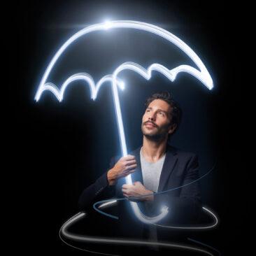 Le visu principal de la campagne Bâloise, un homme sur un fond noir qui tient un parapluie qui se forme par la lumière.